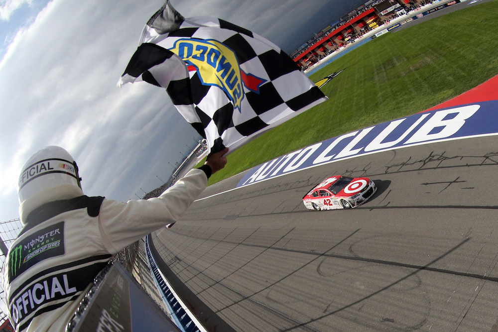 FONTANA, CA - MARCH 26: Kyle Larson, driver of the #42 Target Chevrolet, takes the checkered flag to win the Monster Energy NASCAR Cup Series Auto Club 400 at Auto Club Speedway on March 26, 2017 in Fontana, California. (Photo by Chris Graythen/Getty Images)