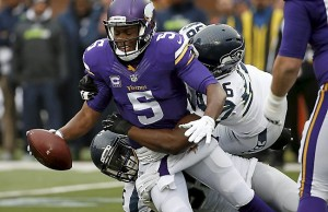 Minnesota Vikings quarterback Teddy Bridgewater (5) is sacked by Seattle Seahawks defenders in the first half of an NFL football game Sunday, Dec. 6, 2015 in Minneapolis. (AP Photo/Ann Heisenfelt)