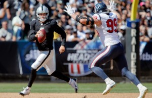 OAKLAND, CA - SEPTEMBER 14:  Rookie quarterback Derek Carr #4 of the Oakland Raiders looks for a receiver under pressure from defensive end J.J. Watt #99 of the Houston Texans late in the second quarter on September 14, 2014 at O.co Coliseum in Oakland, California.  (Photo by Brian Bahr/Getty Images)